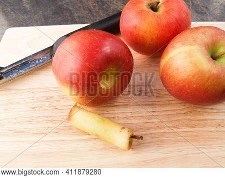 A Fresh Apple Being Prepared By Having The Core Removed On A Wooden Copping Board