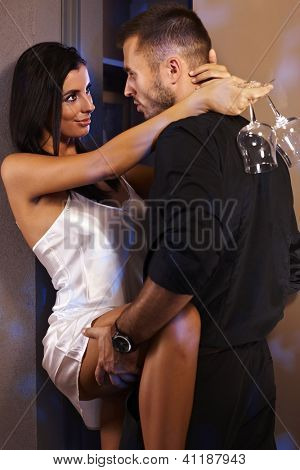 Sexy woman in silk nighty holding champagne flute, embracing with man in black.