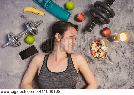 Healthy Asian Woman Smiling In Sportswear Lying On The Floor With Exercise Equipment And Salad Fruit