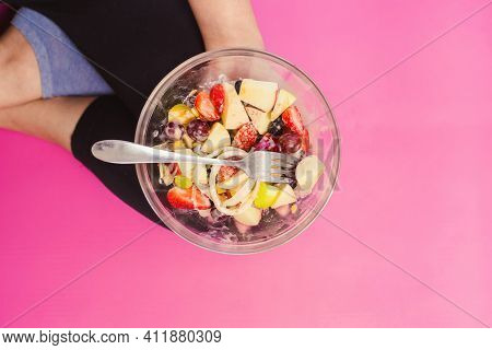 Fitness Sport Woman In Fashion Sportswear Eating Healthy Salad Fruit Bowl. Top View Bowl Fruit Salad