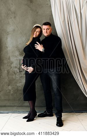 Beautiful Pregnant Couple Dressed In Beautiful Black Clothes Hugs. Pregnant Woman In A Dress Hugs He