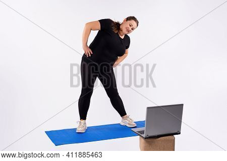 Plus Size Woman Doing Exercises For Weight Loss, At Home On A Fitness Mat In Front Of A Laptop. Onli