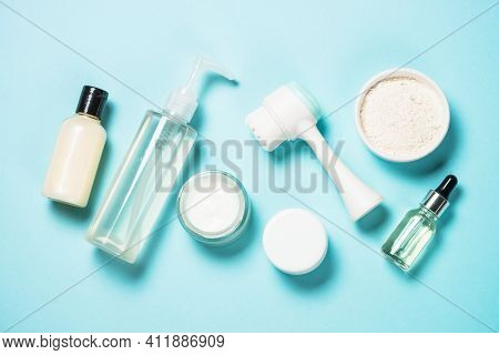 Beauty Product. Face Massage Brush, Cream For Face, Clay Mask And Tonic On Blue Background. Skin Car