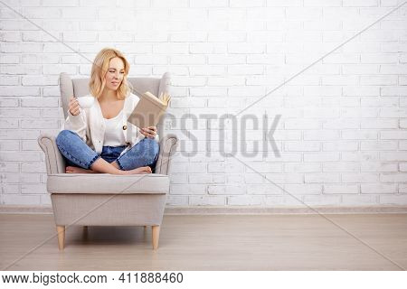 Young Beautiful Woman Sitting In Armchair, Drinking Coffee And Reading Book - Copy Space Over White