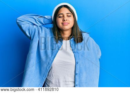 Young latin woman wearing cute wool cap suffering of neck ache injury, touching neck with hand, muscular pain