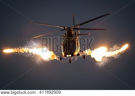 Military Helicopter In Flight Firing Off Flare Decoys At Night.