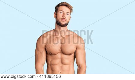 Young caucasian man standing shirtless relaxed with serious expression on face. simple and natural looking at the camera.
