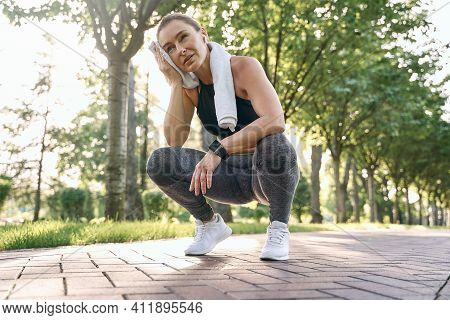 Dont Stop. Tired Middle Aged Athletic Woman In Sportswear Wiping Her Sweat With Towel After Running