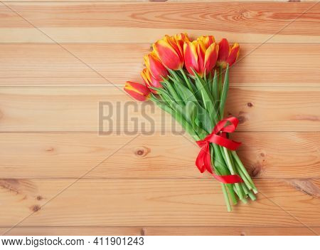 Bouquet Of Fresh Tulips With Red Ribbon On Wooden Background. Top View, Copy Space.
