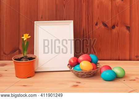 Easter Concept. Little Daffodil In Flower Pot, Easter Eggs In Wicker Basket And White Frame On Woode