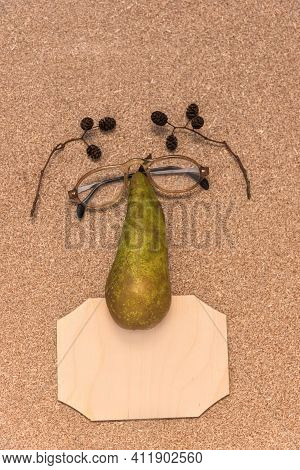 A Face Made Of Glasses, A Pear And A Wooden Plaque On Cork Table. Eyebrows Are Made From Alder Cones