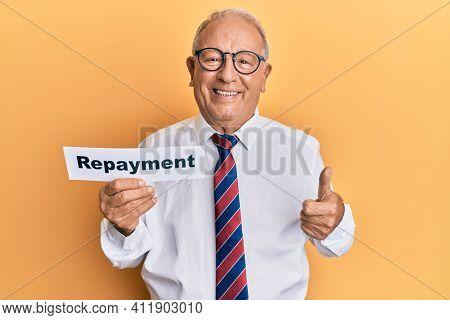 Senior caucasian man holding repayment word paper smiling happy and positive, thumb up doing excellent and approval sign