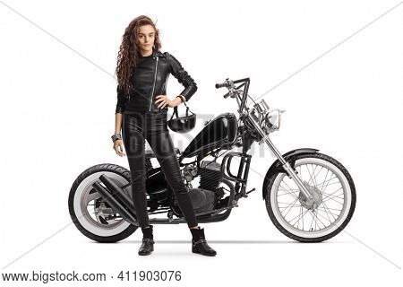 Female biker holding a helmet and posing with a chopper motorbike isolated on white background