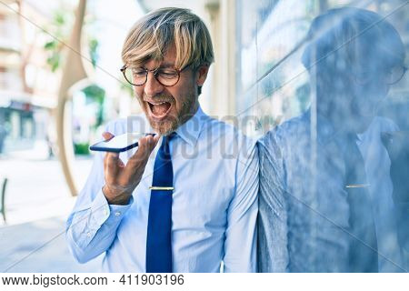 Caucasian business man wearing suit and tie smiling happy outdoors sending voice message using smartphone
