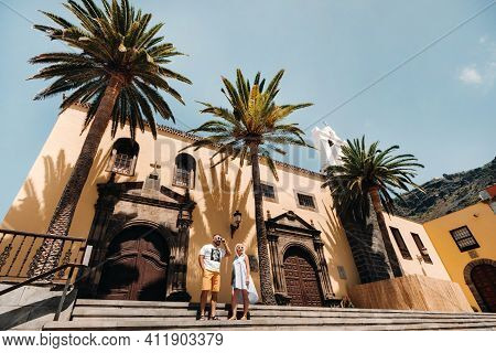 A Girl And A Man Walk In The Old Town Of Garachico On The Island Of Tenerife On A Sunny Day.a Family