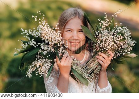 A Beautiful Nine-year-old Blonde Girl With Long Hair In A Long White Dress, Holding A Bouquet Of Lil