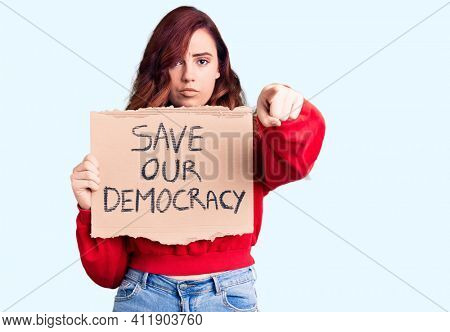 Young beautiful woman holding save our democracy protest banner pointing with finger to the camera and to you, confident gesture looking serious