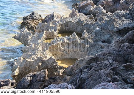 Stone Craters On The Coast Of The Sea On The Island Of Mallorca, Volcanic Coast, Water In The Crater