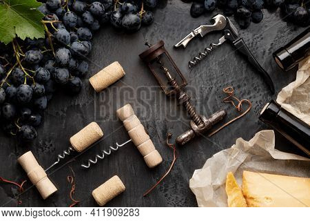 Many Different Corkscrews With Open Wine Corks On Dark Concrete Background In Frame Made Of Black Gr