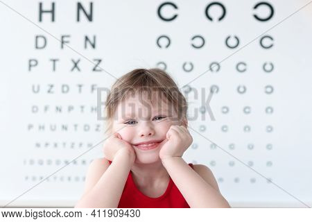 Smiling Little Child Against Vision Test Table In Medical Clinic Portrait. Health And Happy Childhoo