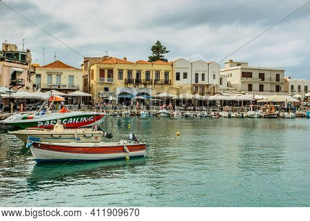 Rethymno, Crete - October 9, 2019. View Of Rethymno Venetian Harbor With Fishing Boats, Colorful Hou