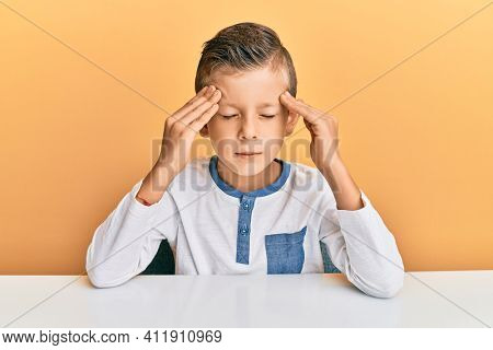 Adorable caucasian kid wearing casual clothes sitting on the table with hand on head for pain in head because stress. suffering migraine.