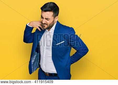 Young hispanic man wearing business jacket suffering of neck ache injury, touching neck with hand, muscular pain