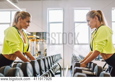 Woman Do Exercises With Dumbbells In Fitness Center Or Gym And Look At Her Reflectionin Mirror. Chal