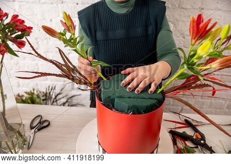 Florist Workplace On The Background Of A White Brick Wall. An Experienced Florist Inserts Cut Flower
