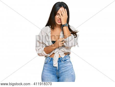 Young beautiful hispanic girl wearing casual clothes yawning tired covering half face, eye and mouth with hand. face hurts in pain.
