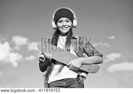 Enjoy Skateboarding. Happy Child Hold Penny Board On Blue Sky. Sport And Activity. Transportation. S