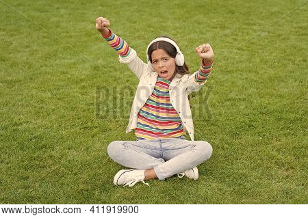 Happiness Is Not Something You Sit Back And Wait. Listen Music While Relaxing Outdoor. Child Headpho