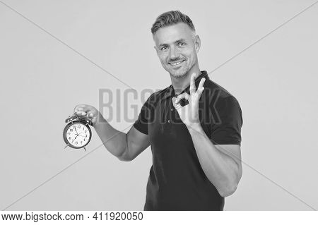 All Right. Happy Man Hold Alarm Clock Showing Ok Sign. Punctuality And Accurate Timekeeping. Chronom