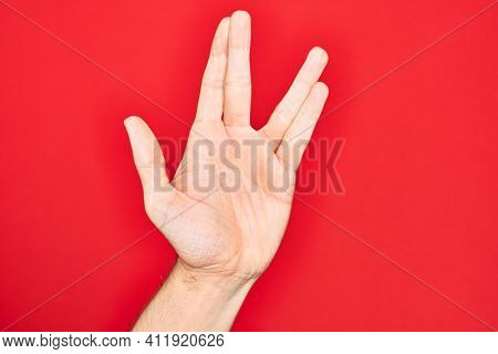 Hand of caucasian young man showing fingers over isolated red background greeting doing Vulcan salute, showing hand palm and fingers, freak culture