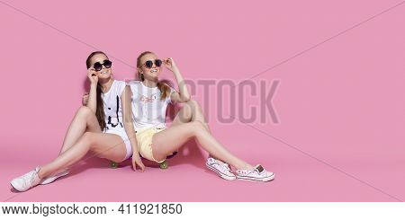Two Girl Skaters Go Crazy And Have Fun Together. Beautiful Sporty Women, Positive Emotion. Pink Back