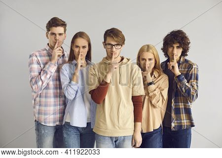 Group Of Serious Young People Doing Shush Gesture Asking You To Keep Their Secret