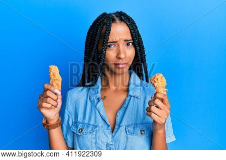Beautiful hispanic woman eating chicken wings skeptic and nervous, frowning upset because of problem. negative person.