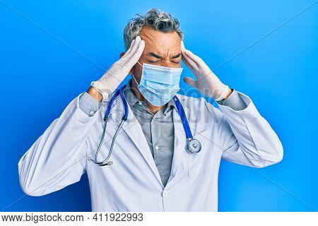 Middle age grey-haired man wearing doctor uniform and medical mask with hand on head, headache because stress. suffering migraine.