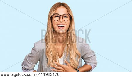 Beautiful blonde young woman wearing business clothes smiling and laughing hard out loud because funny crazy joke with hands on body.