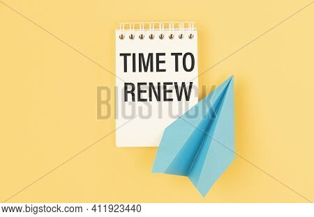 Notepad With The Text Time To Renew On A Yellow Background, And Paper Plane.