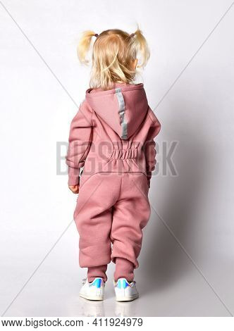 Back View Little Cute Blonde In Pink Warm Comfortable Jumpsuit With A Hood Stands Against A Gray Wal