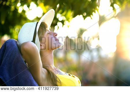 Young Woman Relaxing Outdoors On Sunny Summer Day. Happy Lady Lying Down On Comfortable Beach Chair