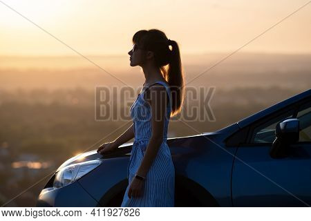 Young Female Driver Resting Near Her Car Enjoying Warm Summer Evening. Travel And Getaway Concept.