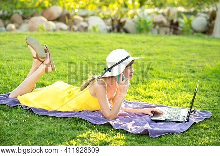 Girl Student In Yellow Summer Dress Resting On Green Lawn In Summer Park Studying On Computer Laptop