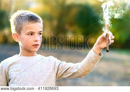 Child Boy Playing With Smoking Wooden Stick Outdoors.