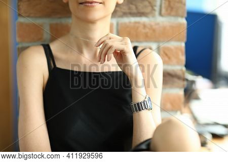 Close Up Woman In A Stylish Dress Leans On A Brick Wall. Slim Model Shows A Chain On The Neck