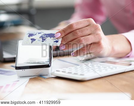 Close-up Of Employee Holding Credit Card. Manager Helping Pay For Service Using Terminal. Worker Giv