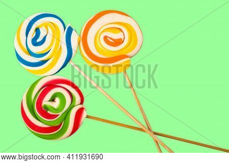 Three Sweet Colourful Lollipops Isolated Over Green Background