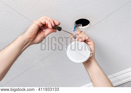 Electrician Hands Repairs Or Installs With Screwdriver The Modern Led Light Bulb On The Ceiling Clos