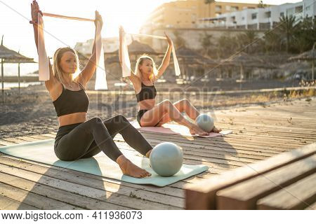 Two Fit Women Practice Yoga Or Pilates Together On The Beach During Sunrise. Real People. Healthy Li
